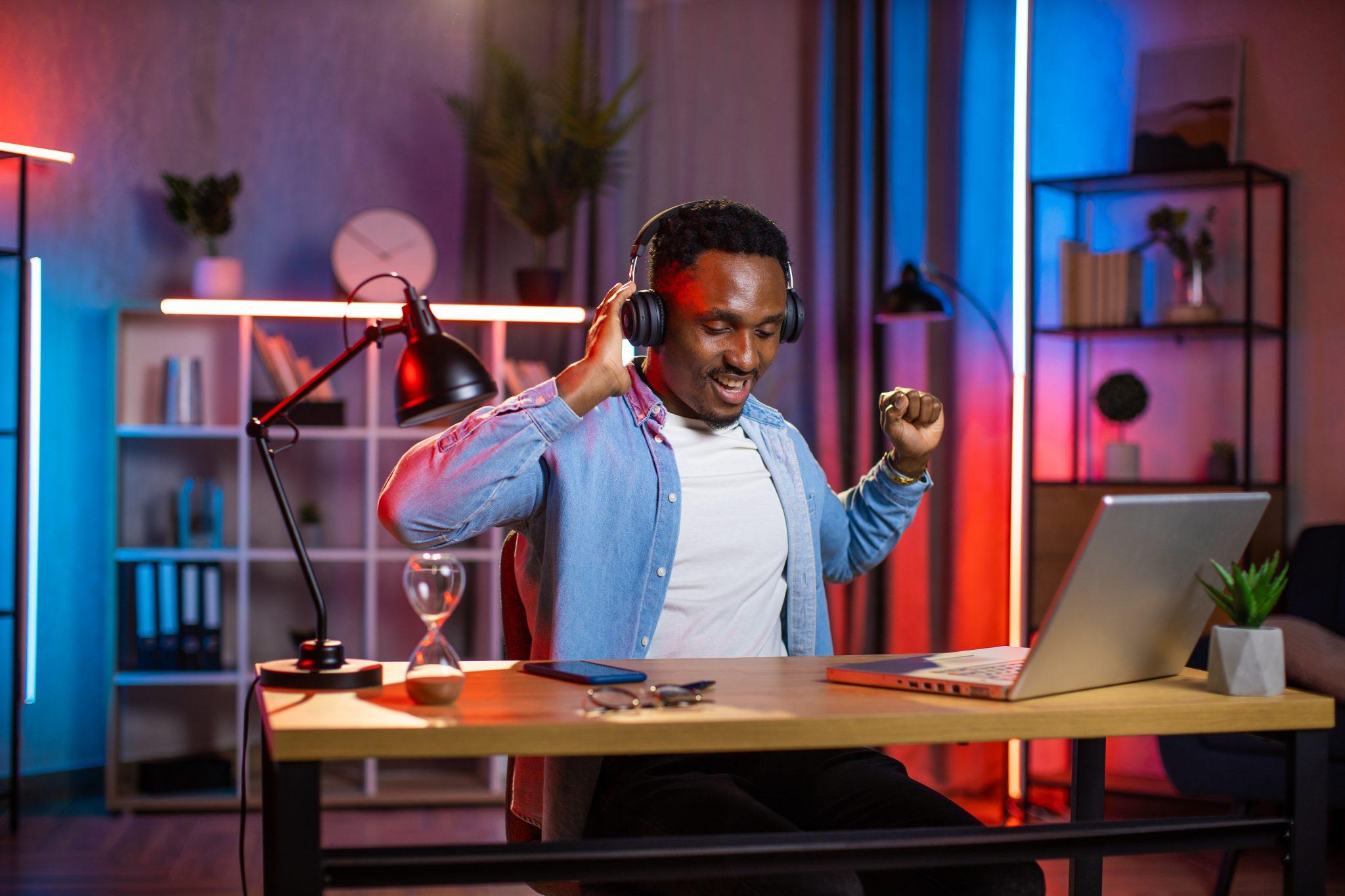Positive african man listening music in wireless headphones